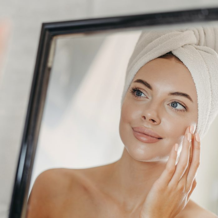 Young naked European woman touches soft skin on face, looks at herself in bathroom mirror, wears wrapped white towel on head after taking bath, poses bare shoulders. Beauty and skin care concept